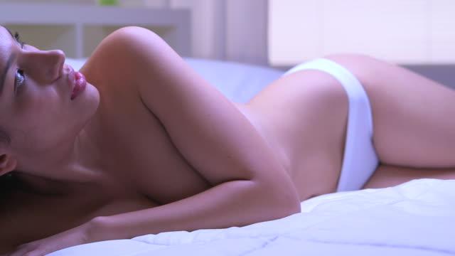 stockvideo's en b-roll-footage met beautiful mexican woman lying in bed - menselijke mond