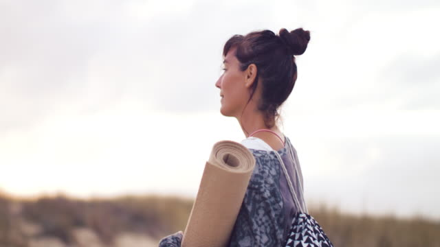 beautiful mid adult woman looking out over ocean, smiling at camera with yoga matt on the dune at sunset at atlantic ocean in the south of france. - roll over stock videos and b-roll footage