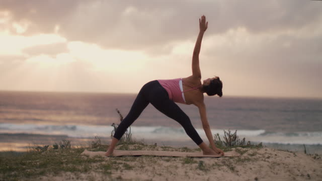 vidéos et rushes de beautiful mid adult woman practicing yoga on the beach at sunset at atlantic ocean in the south of france. - zen