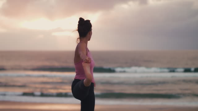 Beautiful mid adult woman practicing yoga on the beach at sunset at Atlantic ocean in the south of France.
