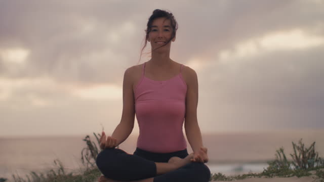 beautiful mid adult woman practicing yoga on the beach at sunset at atlantic ocean in the south of france. - lotussitz stock-videos und b-roll-filmmaterial