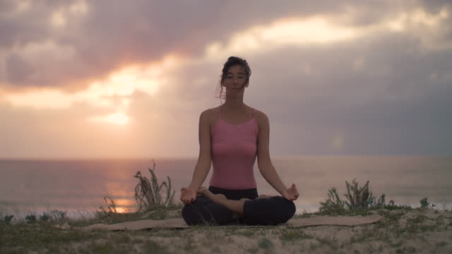 vidéos et rushes de beautiful mid adult woman practicing yoga on the beach at sunset at atlantic ocean in the south of france. - technique de relaxation