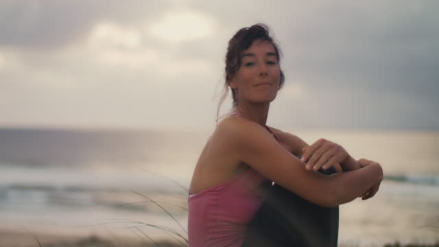 vídeos de stock, filmes e b-roll de beautiful mid adult woman practicing yoga on the beach at sunset at atlantic ocean in the south of france. - mulheres de idade mediana