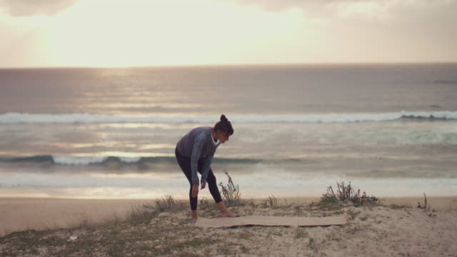 beautiful mid adult woman unrolling yoga matt, practicing yoga on the dune at sunset at atlantic ocean in the south of france. - stare in piedi video stock e b–roll