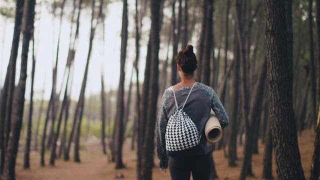 vídeos de stock, filmes e b-roll de beautiful mid adult woman walking with yoga matt in pine forest in the south of france. - mulheres de idade mediana