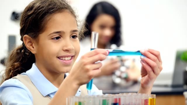 Beautiful middle school girl examines liquid in test tube