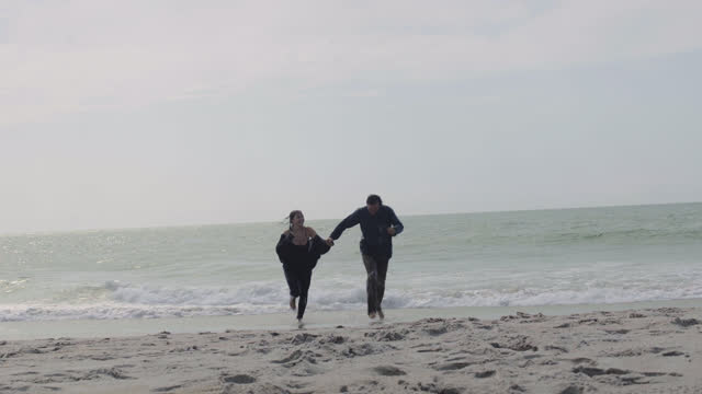 stockvideo's en b-roll-footage met a beautiful millennial couple film themselves running fully clothed in the ocean - north carolina amerikaanse staat