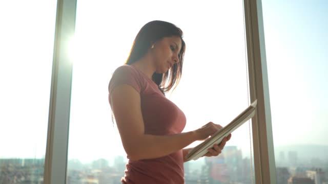 vídeos de stock, filmes e b-roll de fêmea milenar bonita no escritório que lê alguns originais que estão ao lado do indicador - coworking space
