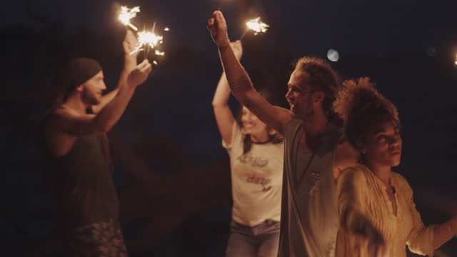 a beautiful millennial group of friends play with sparklers on the beach while camping - 30 34 years stock videos & royalty-free footage