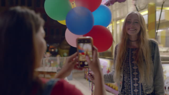 a beautiful millennial woman holding balloons has her picture taken at a carnival - gala stock videos & royalty-free footage