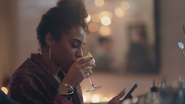 vidéos et rushes de beautiful millennial woman sits alone at a bar drinking, using her phone, and dancing - drink