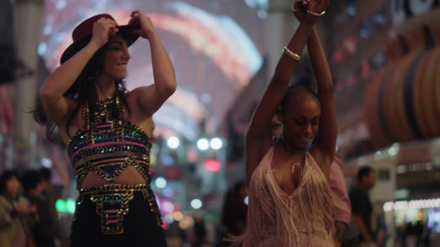 beautiful millennial women dance together with friends on fremont st. in las vegas - millionnaire stock videos & royalty-free footage
