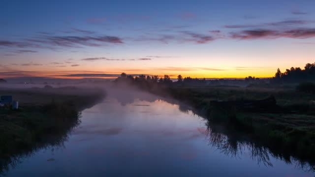 beautiful misty dawn in the summer on the river. timelapse - リフレクション湖点の映像素材/bロール