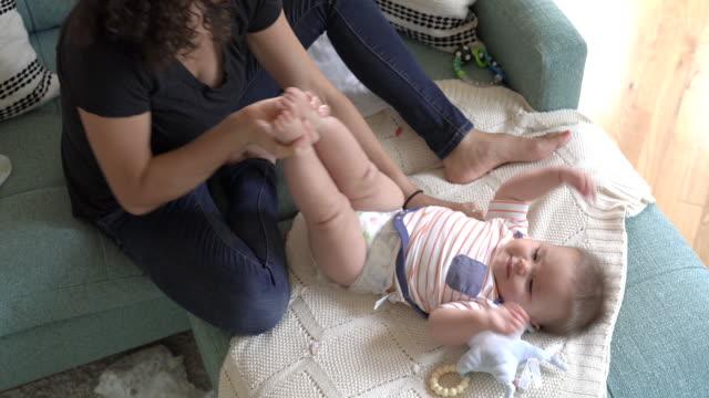 schöne gemischte rasse mutter ändern die windel ihres babys - anziehen stock-videos und b-roll-filmmaterial