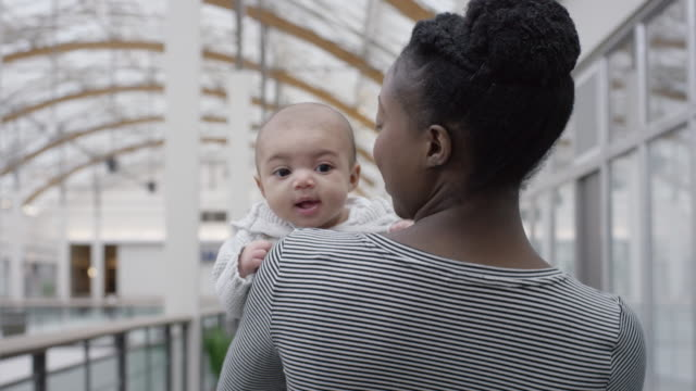 beautiful mixed-race baby girl looks over her mother's shoulder - fatcamera baby stock videos and b-roll footage