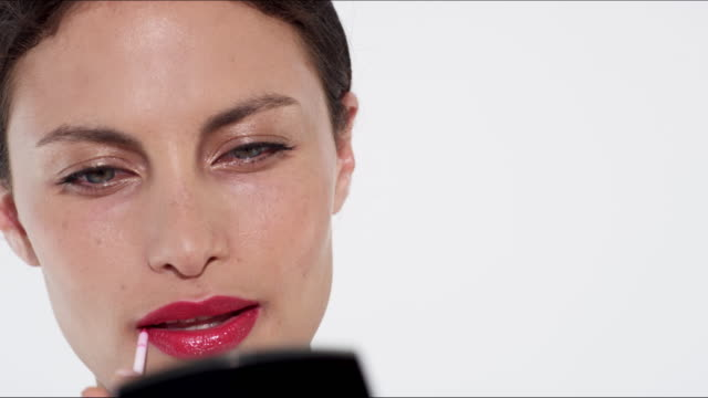 beautiful model in her thirties applying red lipstick - lipgloss stock-videos und b-roll-filmmaterial