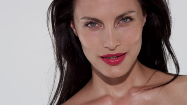 beautiful model with glowing skin and red lips shakes her brunette hair against a white studio background - brown hair stock videos & royalty-free footage