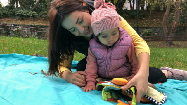 beautiful mom playing with her baby at a park - middle eastern ethnicity stock videos & royalty-free footage