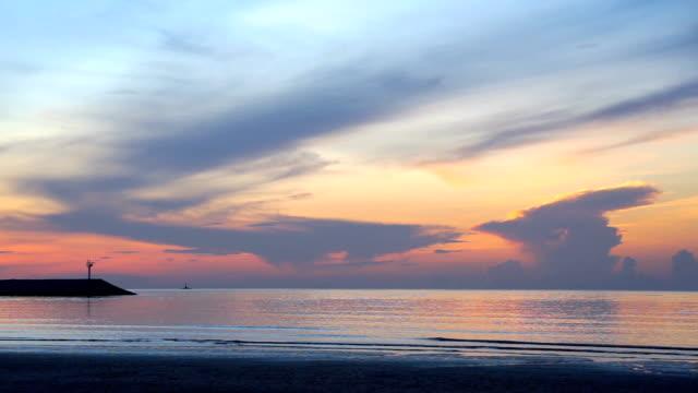 美しい朝の空と海と日没前に灯台のシルエット - ピンク色点の映像素材/bロール
