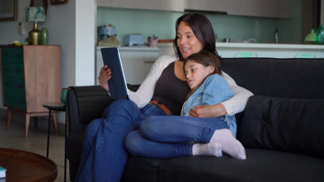 beautiful mother and daughter cuddling on couch while mother reads a story on tablet out loud - using digital tablet stock videos & royalty-free footage