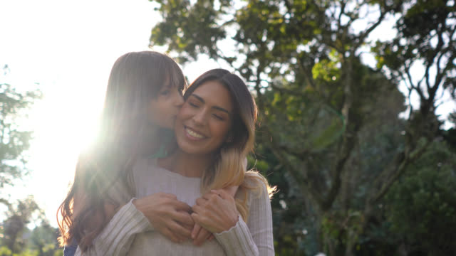 vídeos de stock e filmes b-roll de beautiful mother and daughter hugging each other at the park while facing camera smiling - parque público