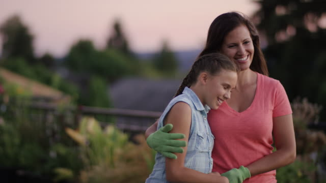 Beautiful mother gardening with her elementary aged daughter