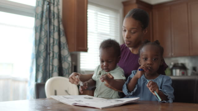 a beautiful mother is colouring in a book with her two children - single mother stock videos & royalty-free footage