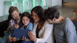 Beautiful mother showing something on tablet to her two kids and husband while sitting down on couch
