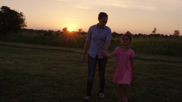 beautiful mother skipping with her daughter in the grass at sunset - skipping along stock videos & royalty-free footage