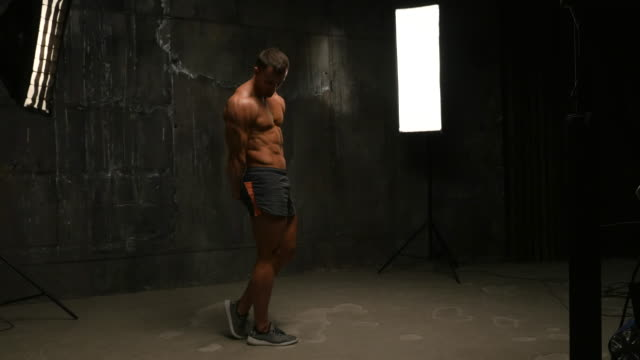 vídeos de stock e filmes b-roll de beautiful muscular man topless shows sports posture - back lit