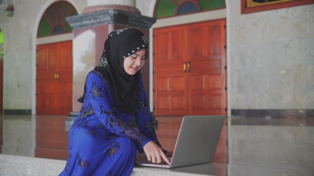 Beautiful Muslim Girl Using laptop computer