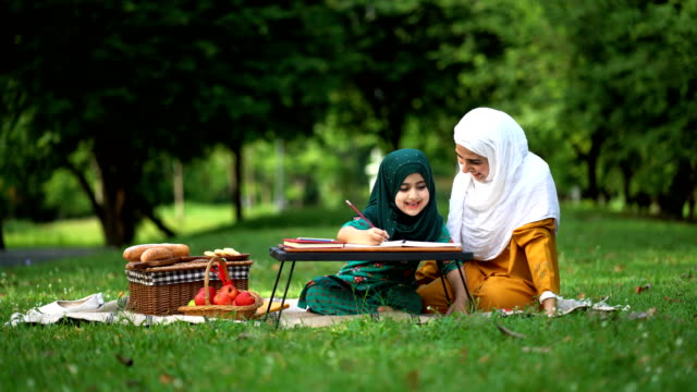beautiful muslim mother teaching a book to her daughter at the park - malaysian ethnicity stock videos & royalty-free footage