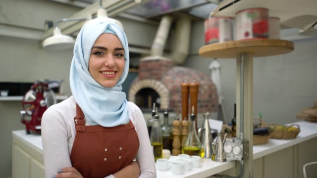 beautiful muslim woman business owner of a restaurant looking at camera smiling with arms crossed - entrepreneur stock videos & royalty-free footage