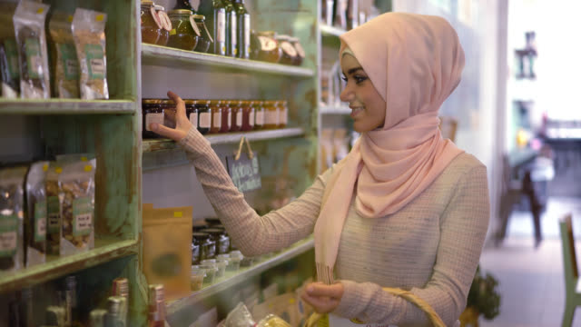 beautiful muslim woman buying groceries at the supermarket - hijab stock videos and b-roll footage