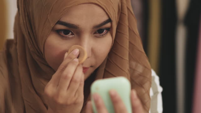 vídeos de stock e filmes b-roll de beautiful muslim woman doing make up on her face - desequilíbrio