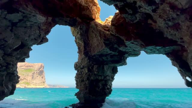 beautiful natural arches cave in the spanish coast with the mediterranean sea. cueva con vistas al mar en la costa blanca de alicante. - mar bildbanksvideor och videomaterial från bakom kulisserna