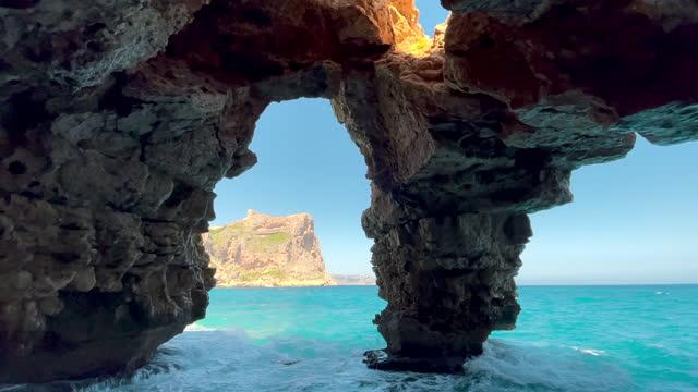 beautiful natural arches cave in the spanish coast with the mediterranean sea. cueva con vistas al mar en la costa blanca de alicante. - mar stock videos & royalty-free footage