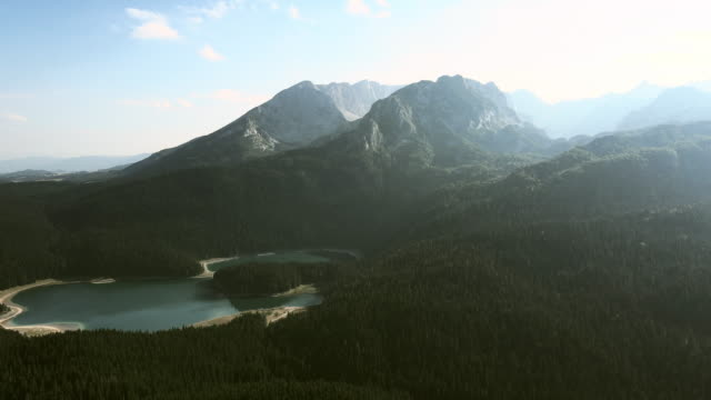 beautiful nature in durmitor mountains, lake and evergreen forest seen through the sun rays - durmitor national park stock videos & royalty-free footage