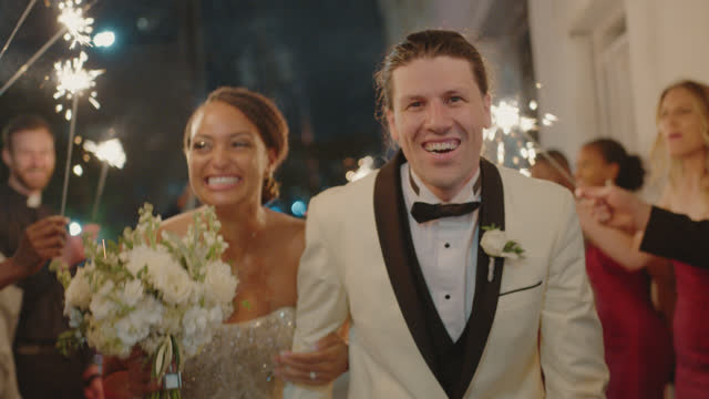 beautiful newlyweds are hit with a rush of emotions as they run through a tunnel of sparklers - husband stock videos & royalty-free footage