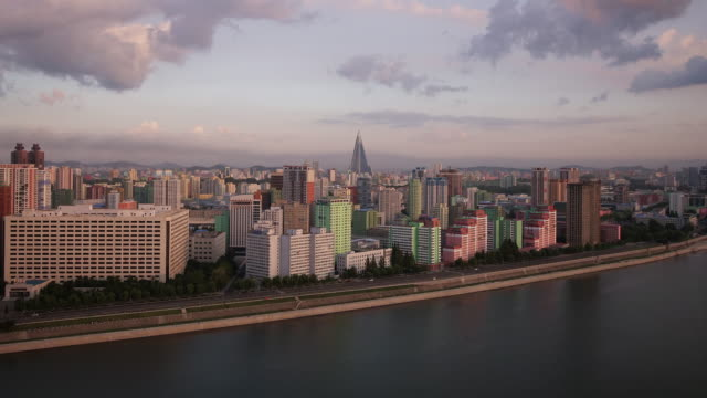 beautiful night to day shot of pyongyang skyline in north korea, drpk. wide shot from above with taedong river and ryugyong hotel (pyramid) - spoonfilm stock videos and b-roll footage