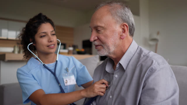 vídeos de stock e filmes b-roll de beautiful nurse checking a senior patient for the stethoscope at home - doctor