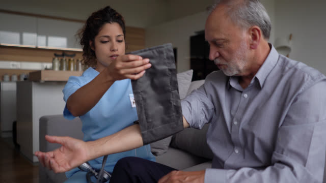 beautiful nurse checking blood pressure of a senior patient at home - healthcare worker stock videos & royalty-free footage