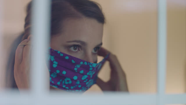 vidéos et rushes de cu of beautiful nurse putting on protective face mask before work. - preparation
