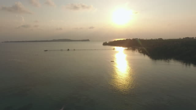 vídeos de stock, filmes e b-roll de oceano bonito e consoles tropicais no nascer do sol, vista aérea - contraluz