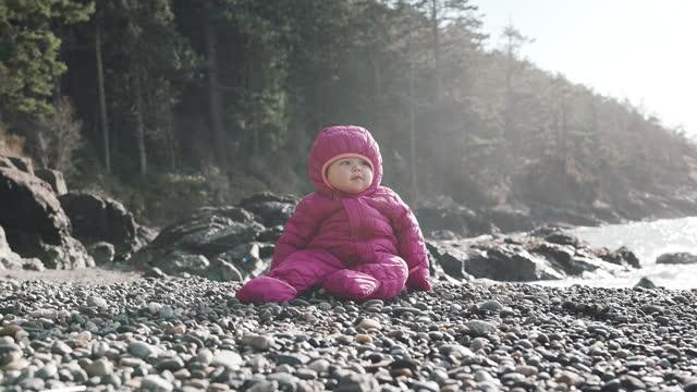 vidéos et rushes de belle fille d'un an s'asseyant par elle-même sur des roches de plage à l'extérieur - bottes