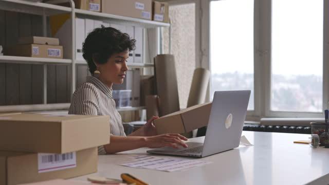 vídeos y material grabado en eventos de stock de hermoso dueño de tienda en línea usando su computadora portátil y preparando pedidos para el envío - vender
