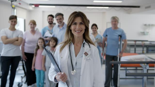 vídeos de stock, filmes e b-roll de ortopedista bonito que sorri na câmera e na equipe dos profissionais e dos pacientes que estão no fundo muito alegre - physical injury