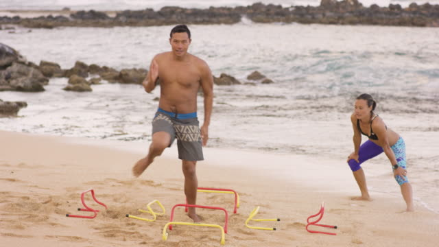 beautiful pacific islander man and woman exercising on beach - pacific islander stock videos & royalty-free footage