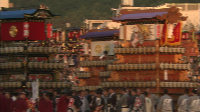 Beautiful pagoda floats decorated with paper lanterns line up for a parade during the Saijo Festival in Japan.
