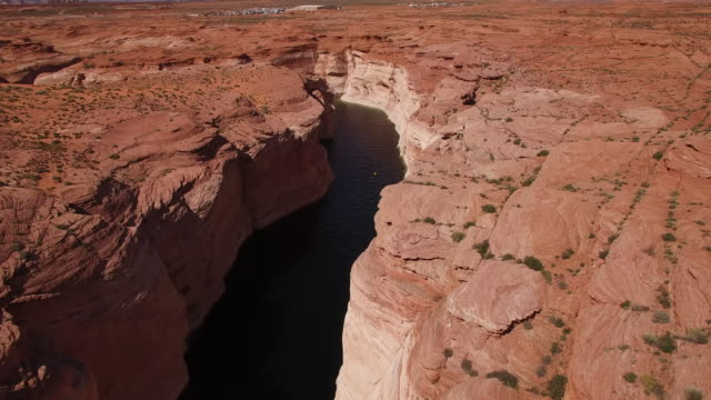 beautiful pan down to kayakers in water canyon lake powell 4k, drone aerial view of kayak and boat on lake powell reservoir and colorado river, with beautiful sand stone grand caonyon and water reflection located in glen canyon, arizona - grand canyon nationalpark stock-videos und b-roll-filmmaterial